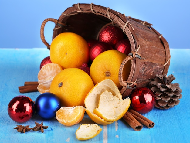 Christmas tangerines and christmas toys in basket on blue background
