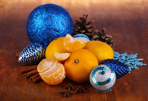 Christmas tangerines and christmas toys on wooden table close-up
