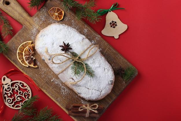 赤い背景にドライフルーツ、ベリー、ナッツでシュトーレンのクリスマスおいしい。伝統的なドイツの御馳走。水平フォーマット。コピースペース