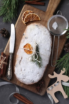 木の板にドライフルーツ、ベリー、ナッツを添えたクリスマスのおいしいシュトーレン。伝統的なドイツの御馳走。上面図 Premium写真