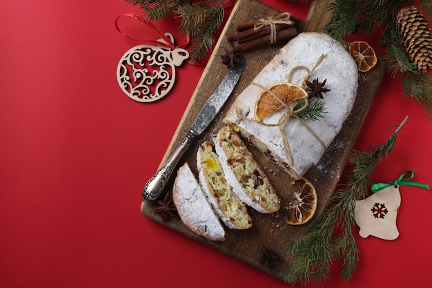 Christmas tasty stollen with dry fruits, berries and nuts on red background. traditional german treats. top view. copy space