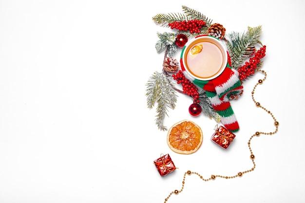 クリスマスティー。カップはスカーフに包まれています。休日。花輪と贈り物。白い表面。新年とクリスマス。スペースをコピーします。モミの枝の花輪。ホットドリンク。
