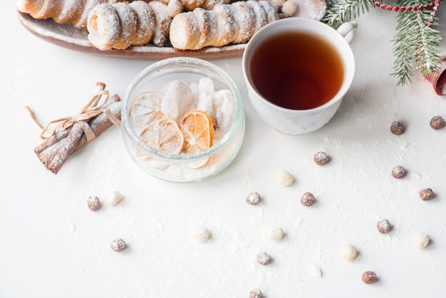 Christmas tea with pastries, a branch of green spruce, scattered biscuits, a snail biscuit with protein cream