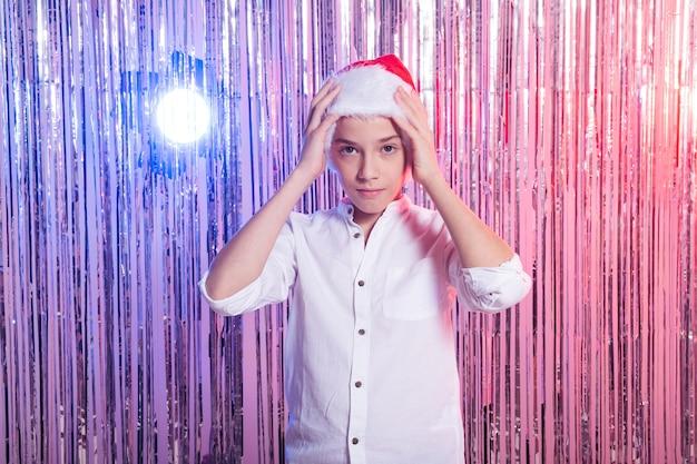 Рождественский мальчик-подросток в шляпе санта-клауса
