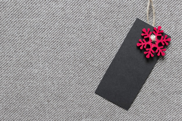 Christmas template mockup with black blank label and red wooden snowflake on textured fabric