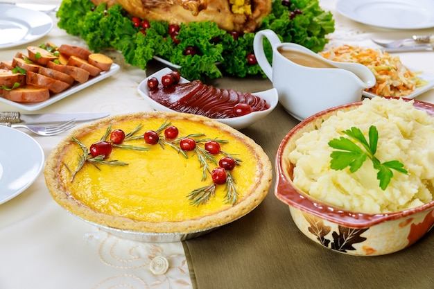 Christmas or thanksgiving dishes pumpkin pie decorated with cranberries and mashed potatoes .