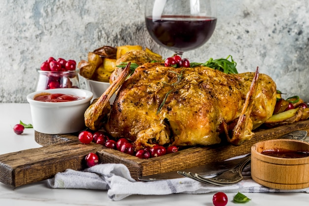 Christmas, thanksgiving food, baked roasted chicken with cranberry and herbs, served with fried vegetables, fresh berries wine and sauces on white marble table, copy space