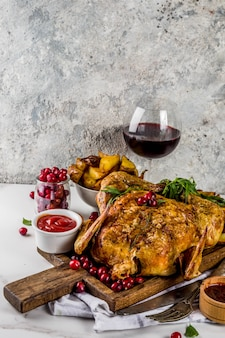 Christmas, thanksgiving food, baked roasted chicken with cranberry and herbs, served with fried vegetables, fresh berries wine and sauces