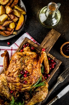 Christmas thanksgiving food baked roasted chicken with cranberry and herbs served with fried vegetables and sauces on dark rusty table