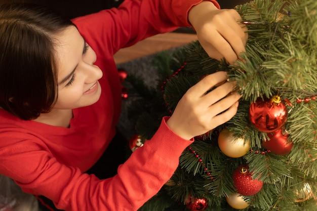 クリスマスのテーマ。若い女性がおもちゃやボールで木を飾ります。