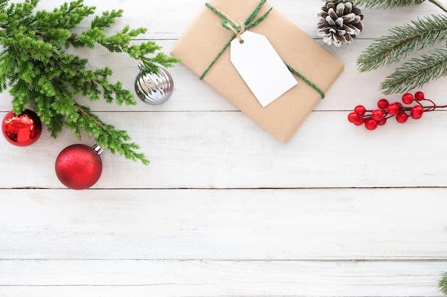 クリスマスのテーマの背景。クリスマスプレゼントギフトボックス、モミの枝、クリスマスボール、ホリーベリーと松のコーンの装飾は、木製の木製の素朴な要素。クリエイティブフラットレイ、トップビューデザイン