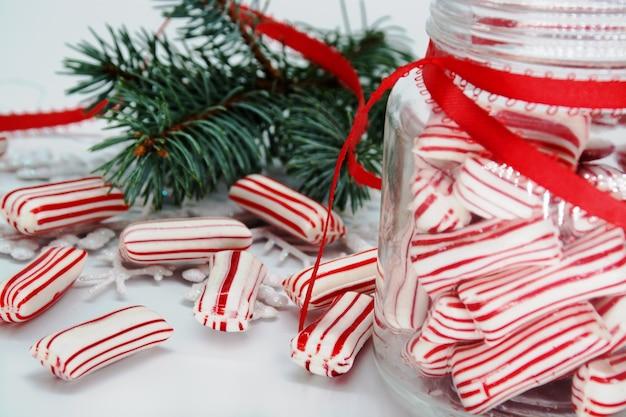 크리스마스 테마 배경입니다. 항아리와 테이블에 크리스마스 줄무늬 사탕입니다.