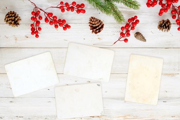 クリスマスのテーマの背景には、白い木のテーブルに空白の写真の紙と装飾要素。クリエイティブなフラットなレイアウトと、境界線とコピースペースのデザインによるトップビューの構図。