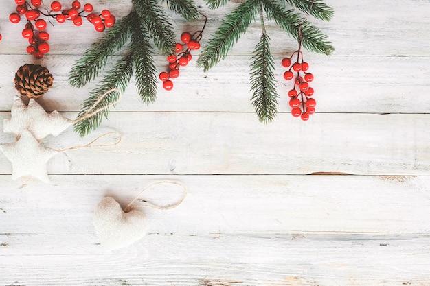クリスマスのテーマの背景には、要素と飾りを装飾白い木のテーブルに素朴。クリエイティブなフラットなレイアウトと、境界線とコピースペースのデザインによるトップビューの構図。