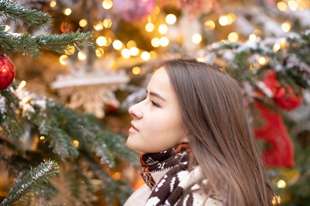 크리스마스 테마입니다. 크리스마스 트리, 조명, 장난감을 배경으로 하는 아름다운 유럽 소녀는 즐거운 분위기, 행복, 선물의 꿈을 꿉니다.