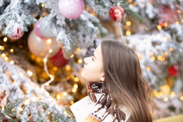 크리스마스 테마. 크리스마스 트리 배경에 젊은 아름 다운 유럽 소녀