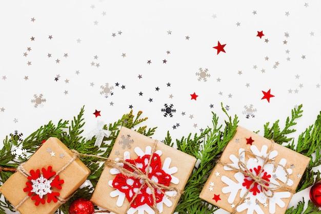 Рождественская туя ветка, украшения и подарки, завернутые в крафт бумажные снежинки. плоская планировка, вид сверху.