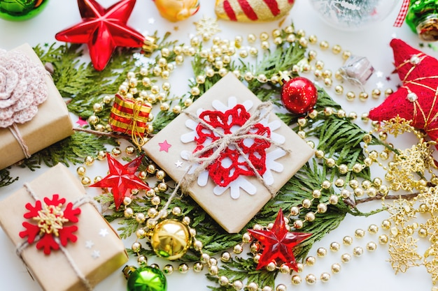 Рождественская туя ветка, украшения и подарки, завернутые в крафт бумажные снежинки.