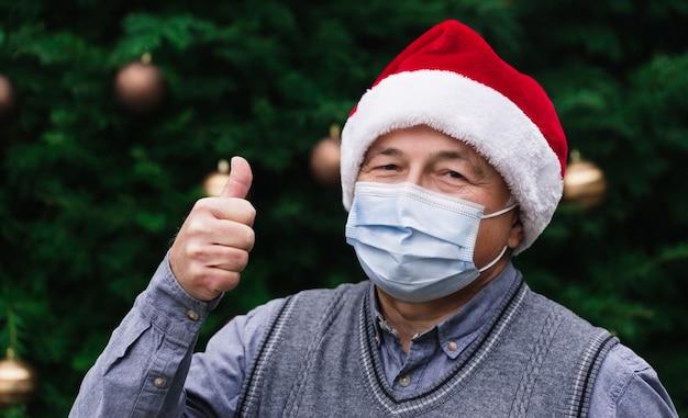 Рождество недурно как знак. крупным планом портрет старшего человека в шляпе санта-клауса и медицинской маске с эмоциями. на фоне елки. коронавирус пандемия