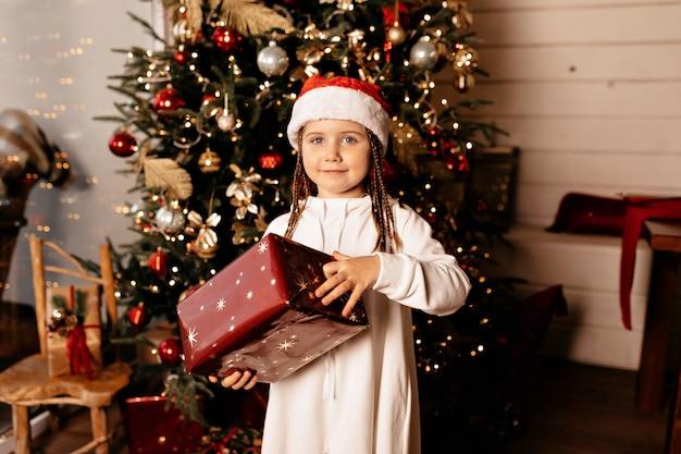 Tempo di natale, bambino allegro in un cappello di natale con il regalo di natale che posa sopra l'albero di natale