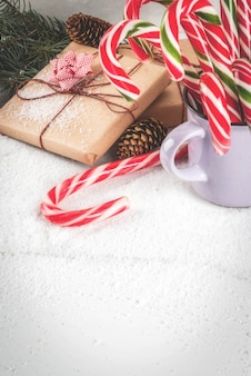 Christmas time concept, christmas tree branches, pine cones, gifts and traditional new year sweets candy cane, on a white marble table with snow.  copyspace