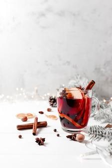 ホワイトグレーのコンクリートの背景のテーブルにホットワインのクリスマスの時期のガラスカップ