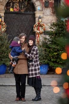 Рождественское время. счастливая семья мать, отец и маленькая девочка, прогулки по городу и с удовольствием. путешествия, туризм, отдых и люди. варшава, польша