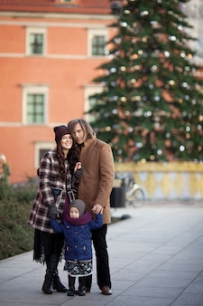 Christmas time. happy family - mother, father and little girl walking in city and having fun
