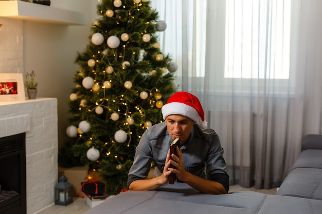 Рождественское время. одинокий мужчина молится. рождественские стены с огнями повесили на елку. праздничное настроение дома зимой.