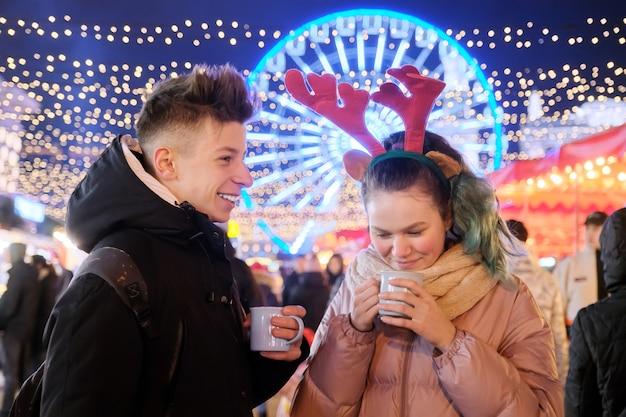 Рождество, новогодние каникулы. молодые люди, пара подростков веселятся на рождественской ярмарке