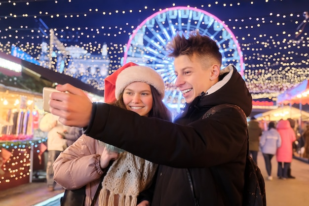 Christmas time, new year holidays. young people, couple of teenagers having fun at christmas market