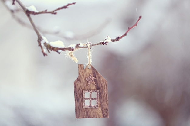 Christmas time. a small wooden house swings on a branch and large flakes of snow fall slowly.