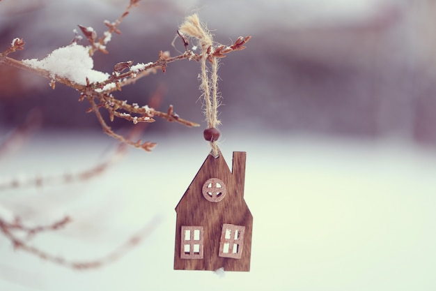 Christmas time. wooden small house on a branch in winter and snow