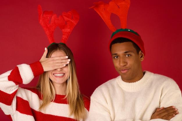 크리스마스 때. 빨간 배경에 뿔이 있는 모자를 쓴 젊은 부부