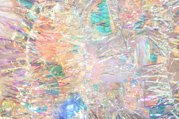 Christmas tinsel garland abstract background in pastel iridescent colors.