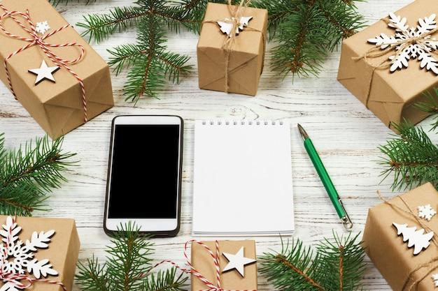 Рождество, чтобы сделать список. смартфон, noteboock, подарочная коробка с красной лентой, список покупок с копией пространства на белом деревянном столе. концепция зимнего отдыха. вид сверху.