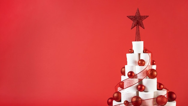 Christmas toilet paper tree on copy space red background