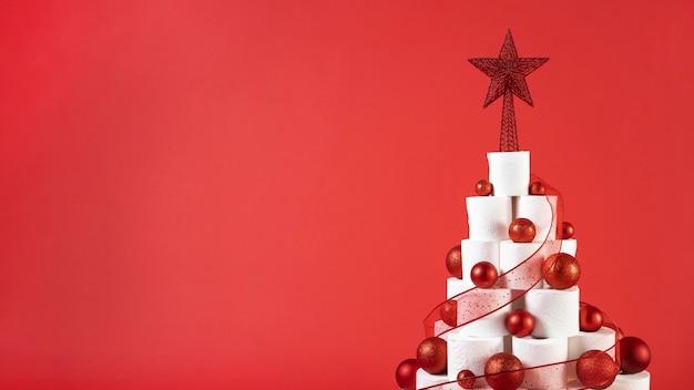 Рождественская елка из туалетной бумаги на красном фоне пространства для копирования