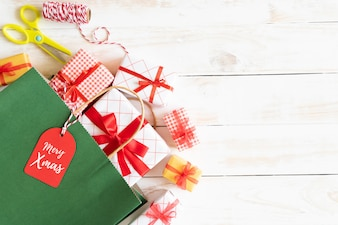 Christmas top view of Gift box and red shopping bag with message tag on a wooden backgroun