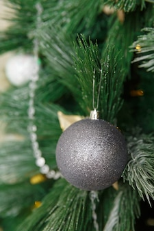 Christmas toy ball hanging on branch of new year tree decorated with garland