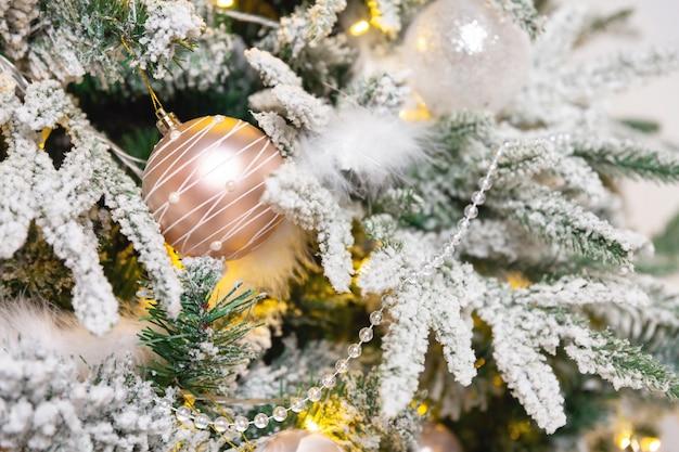 Елочный шар игрушки висит на ветке ели. новогодняя елка украшена гирляндой.