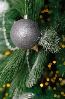 Елочная игрушка мяч висит на ветке ели. новогодняя елка украшенная гирляндой