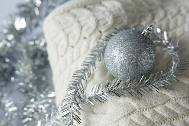 Christmas toy ball with sparkles on knitted woolen sweater