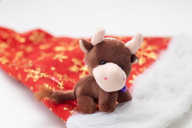 サンタクロースの帽子に2021年の新年のクリスマスのおもちゃの雄牛のシンボル。