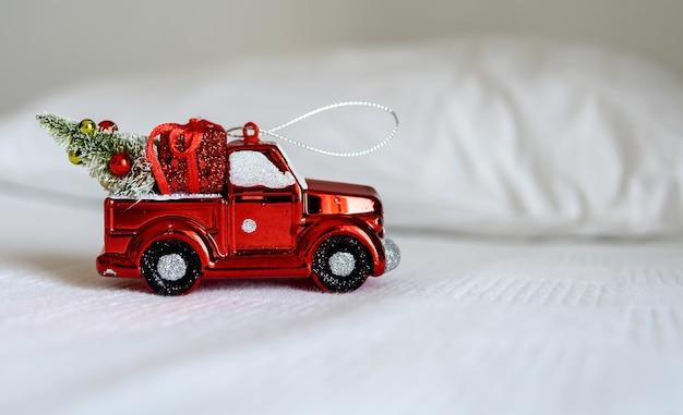 흰색 침대에 크리스마스 장난감 자동차입니다. 해피 크리스마스, 새해, 휴일, 겨울, 인사의 개념.