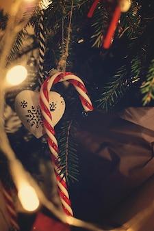 クリスマスのおもちゃのキャラメルは、輝く花輪に囲まれた枝にぶら下がっています。