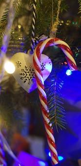 垂直に輝く花輪に囲まれた枝にぶら下がっているクリスマスのおもちゃのキャラメル