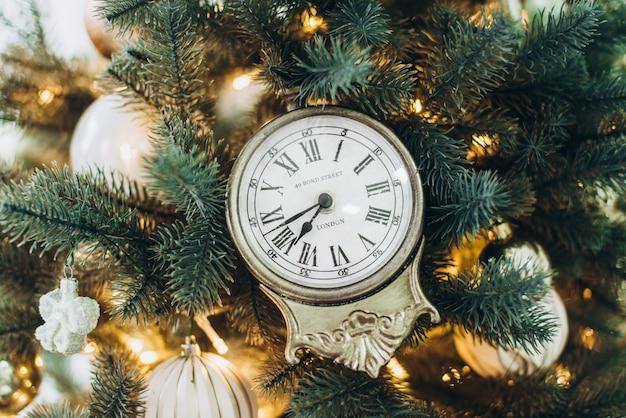 クリスマスツリーに掛かるクリスマスのおもちゃの時計。クリスマスと新年のコンセプト