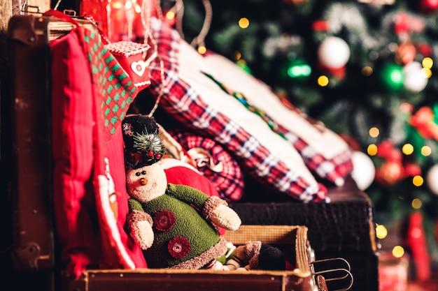 Рождественский игрушечный эльф сидит на чемодане на фоне елки.