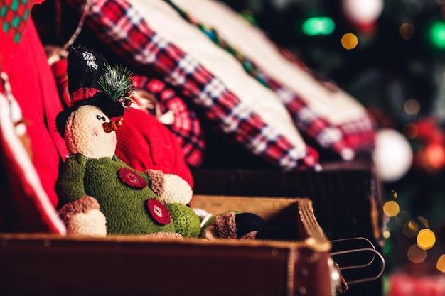 クリスマスツリーの表面のスーツケースに座っているクリスマスのおもちゃのエルフ。